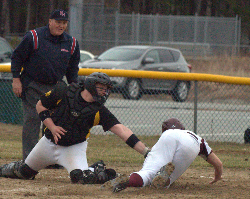 Lebanon's Grayson Hardy is tagged out at home by Souhegan's Cam Crook. For more photos, go to the Photo Album.