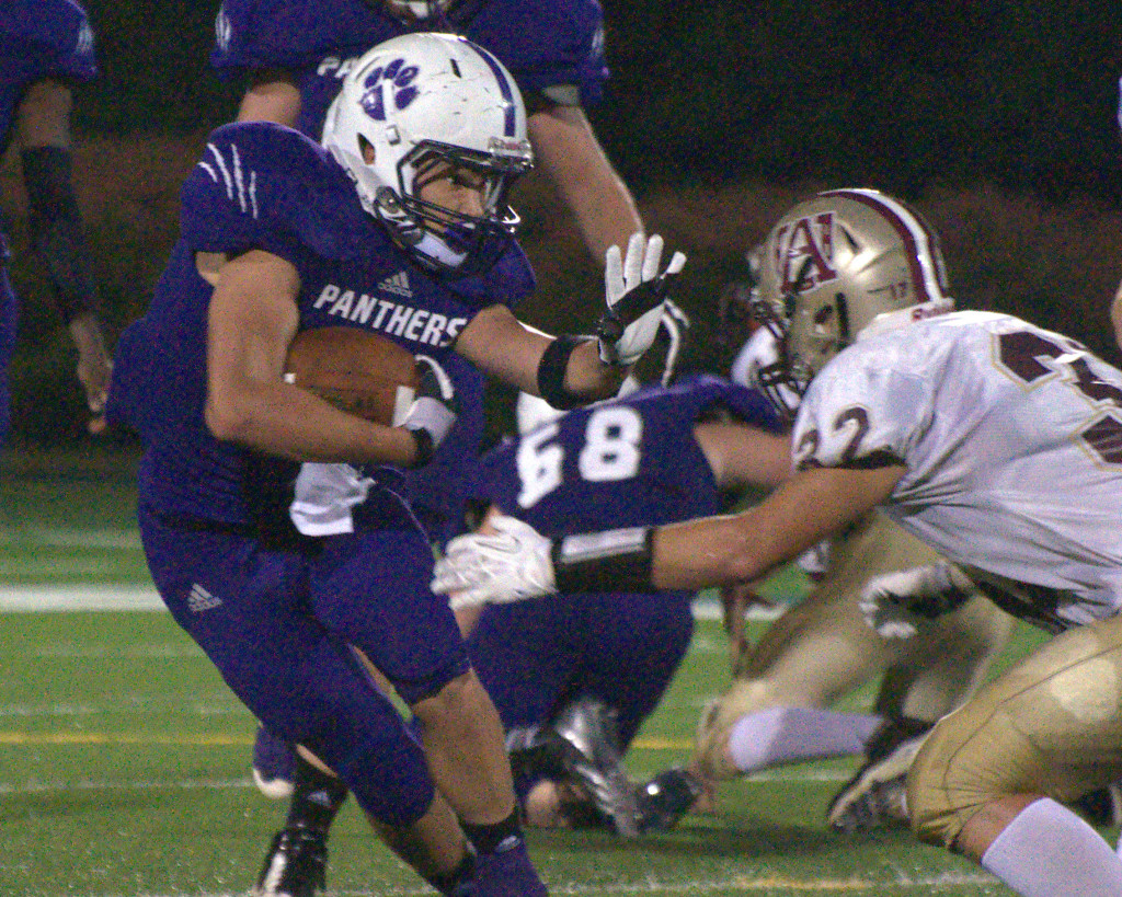 Nashua South's Josh Perry tries to fight off a tackle during Thursday's first half against Alvirne.