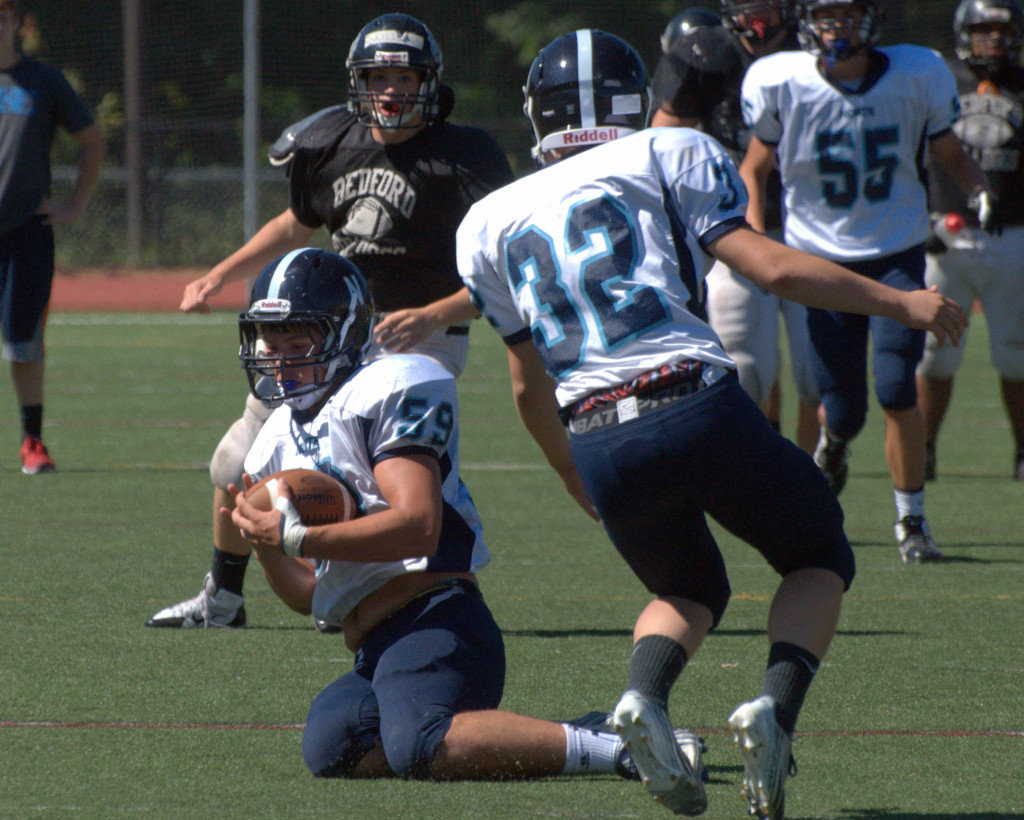 Nashua North's Aaron Stewart (No. 32) watches as teammate Greg Stanton intercepts a pass earlier this year.