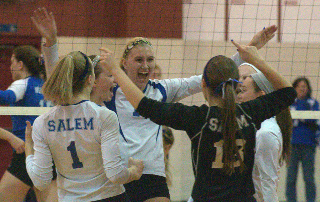 Olivia Burke, center, and the Salem volleyball team celebrate during their semifinal match against Merrimack.