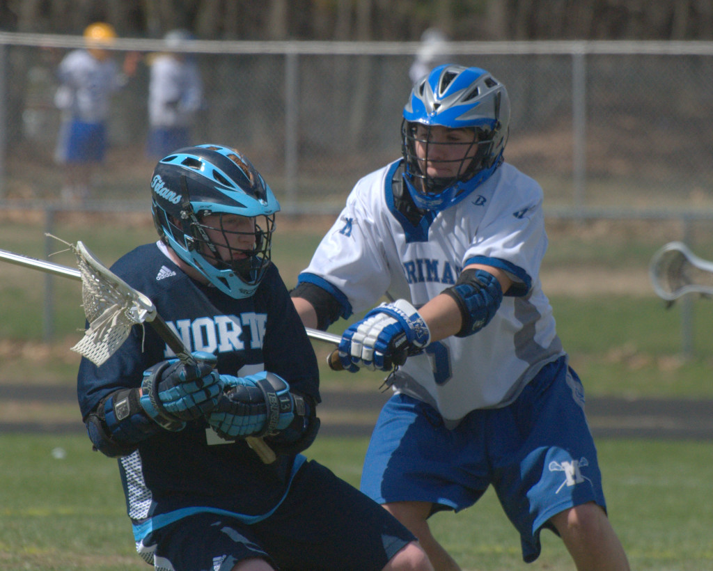 Merrimack's Thomas Perkins tries to slow down Nashua North's Jon Searles during Saturday's game.