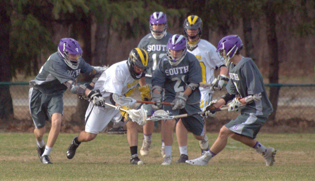 Nashua South players surround a Souhegan player as they go after a groundball during Monday's game.