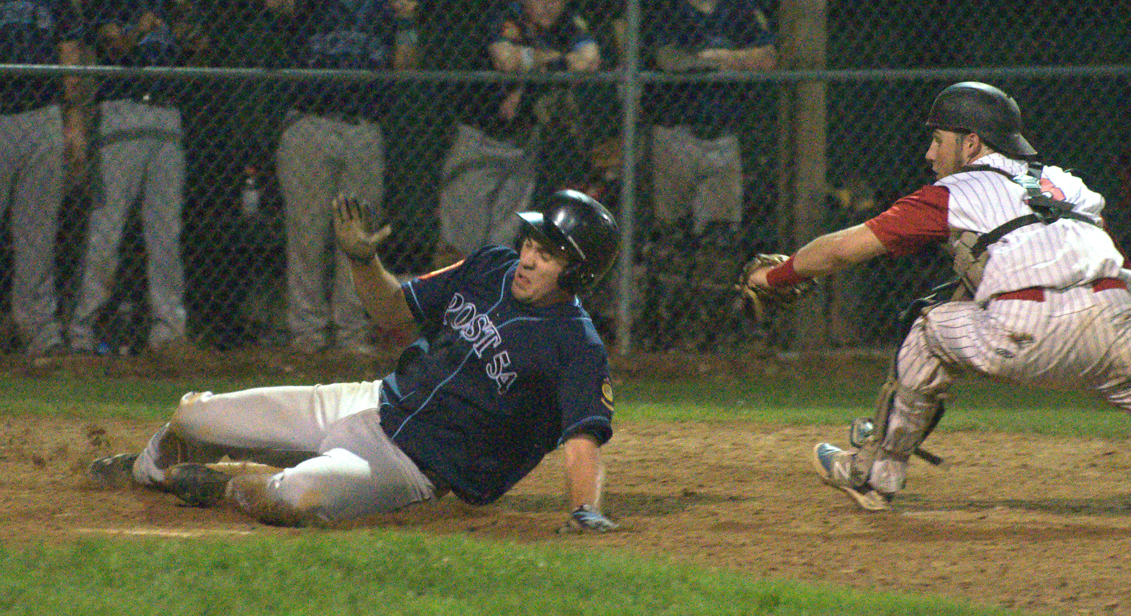 Bedford's Michael Kernan slides safely past Concord catcher Chris Fournier during Thursday's game.