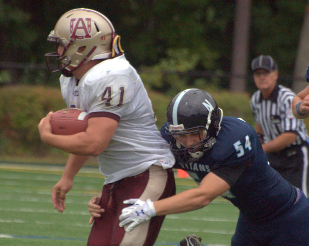 Alvirne's Ethan Rainville drags Nashua North's Phil Pereira for a few yards during Saturday's game.