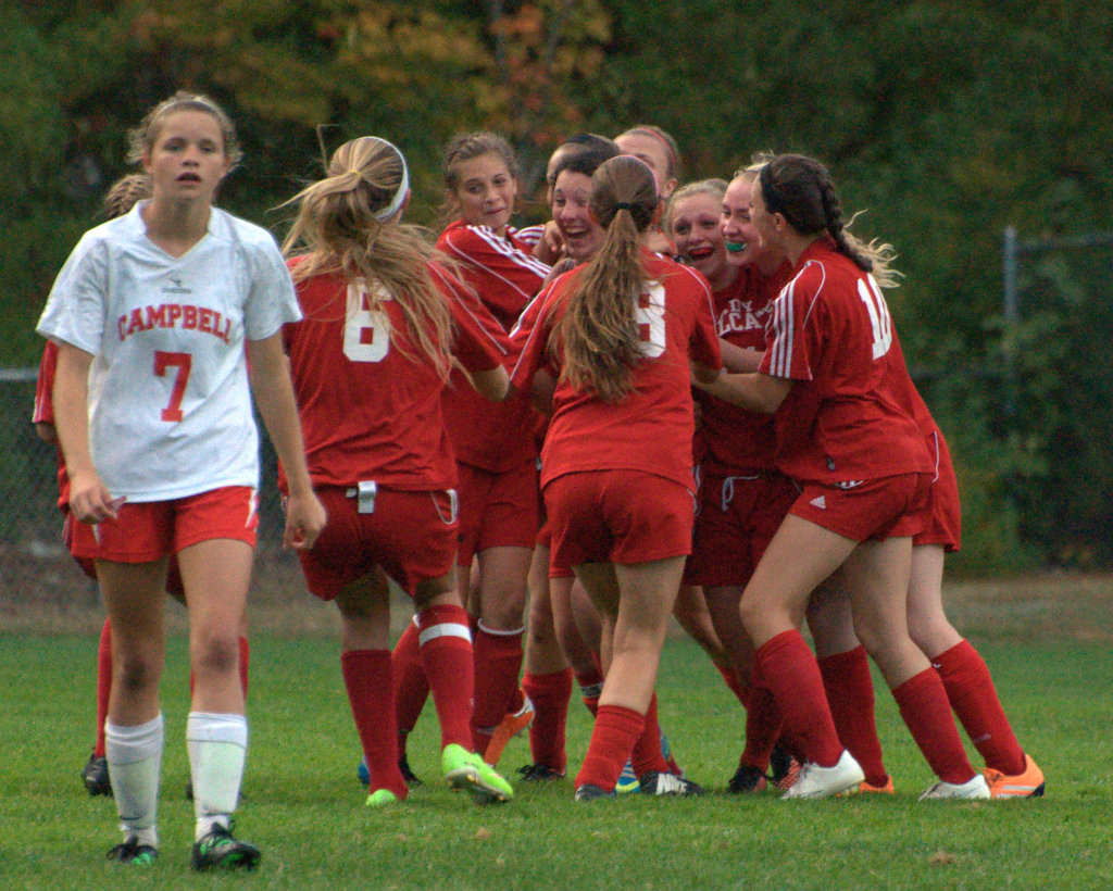 The Hillsboro-Deering girls soccer team celebrates after the game-winning goal as Campbell's Olivia Crema walks off the field on Thursday.
