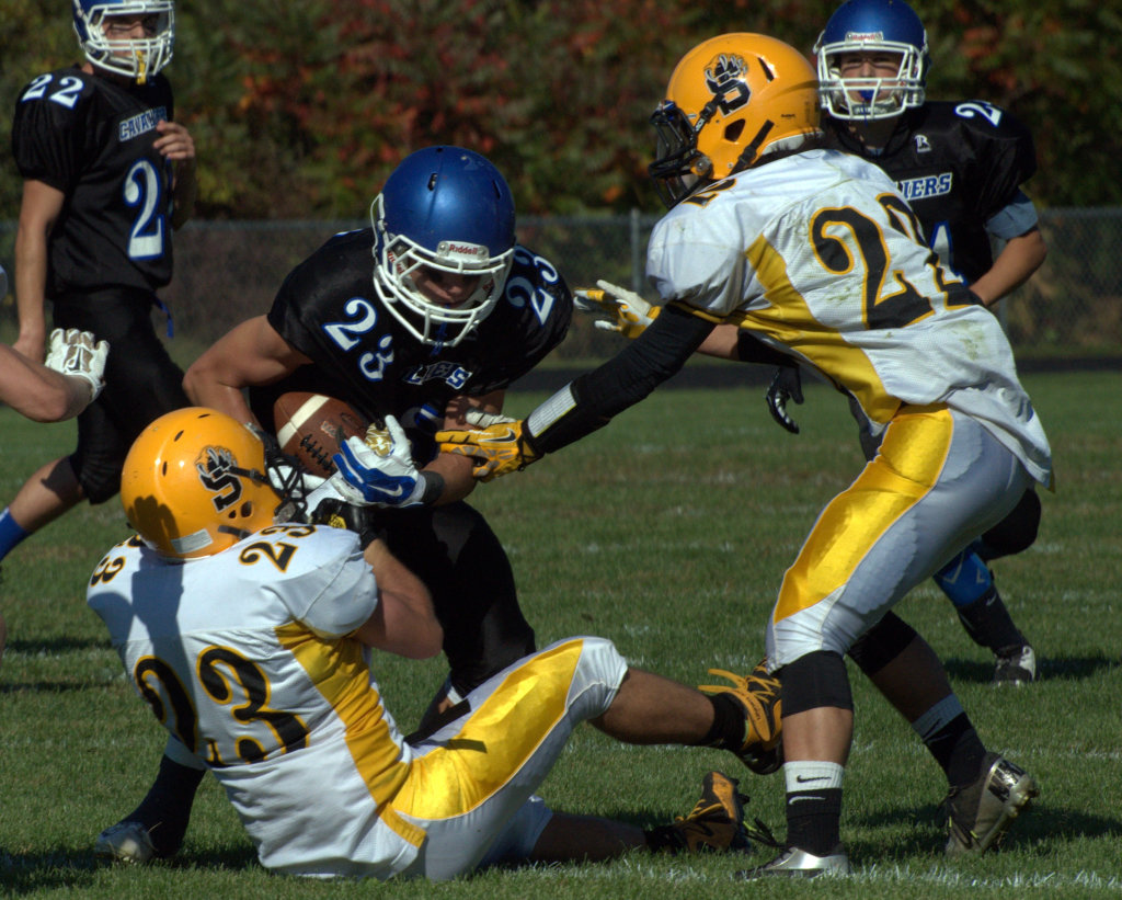 Souhegan's Tucker Aiello, left, and Zach Bossi try to bring down Hollis Brookline's Joe Brooks during Saturday's game.