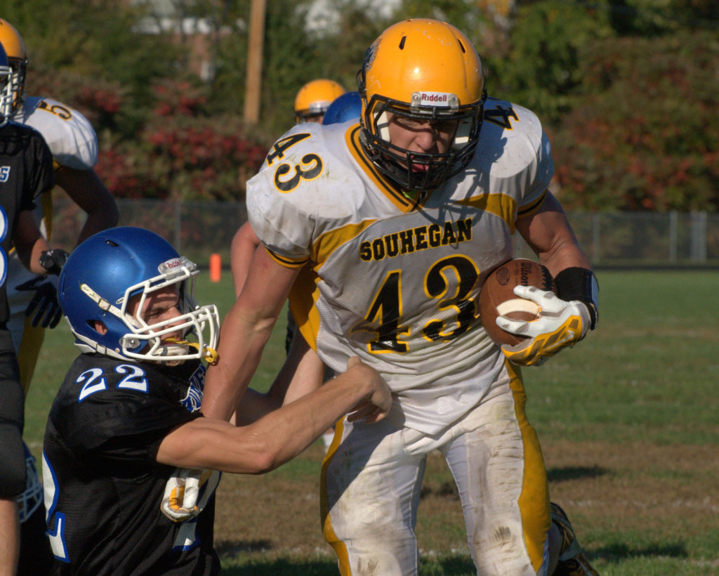 Souhegan's Tyler Howard breaks a tackle by Hollis Brookline's Patch Zorn on his way to the end zone during Saturday's game.