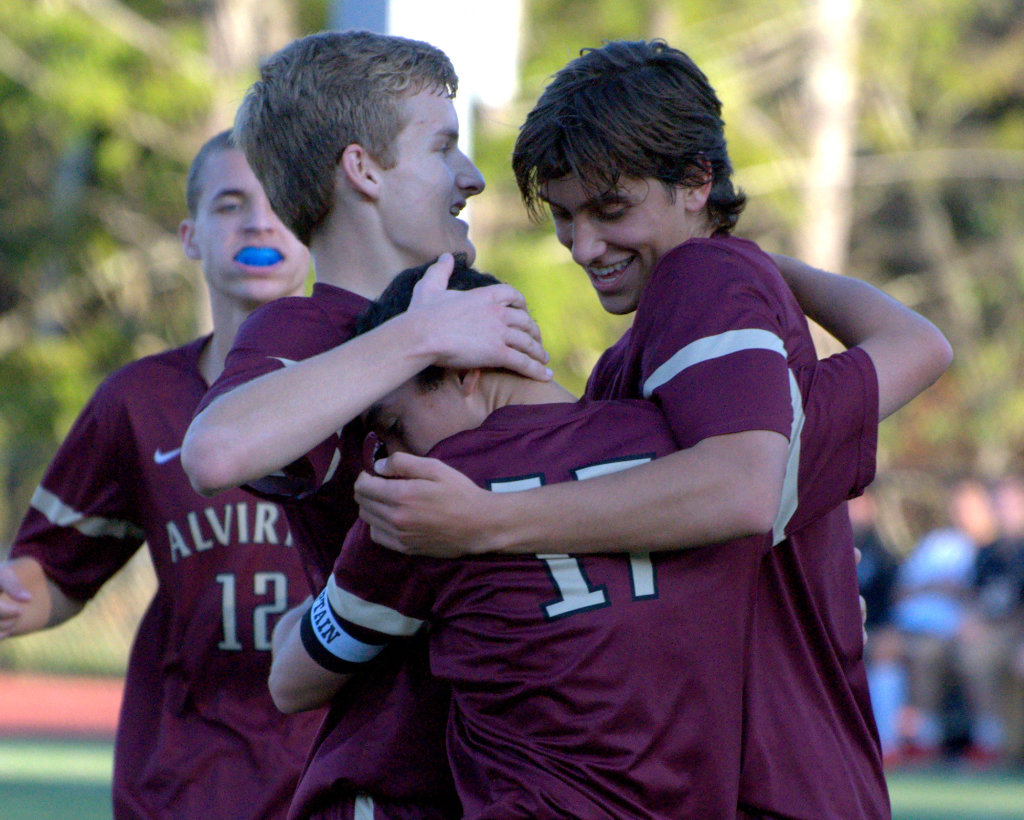 Alvirne's Matt Lubinski, center, is congratulated after his first goal by teammates Nate Gosselin, left, and Raul Stedile during Friday's game at Bedford.