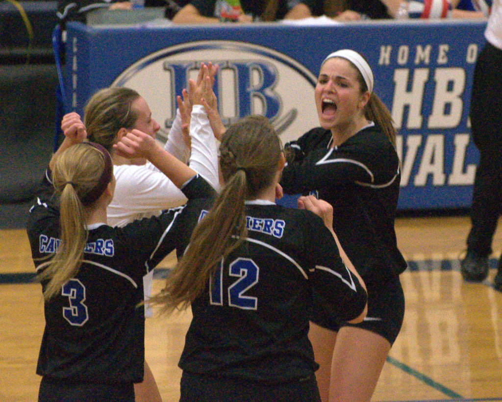Madison Blake, right, celebrates with her Hollis Brookline teammates after winning a point during Wednesday's match against Londonderry.