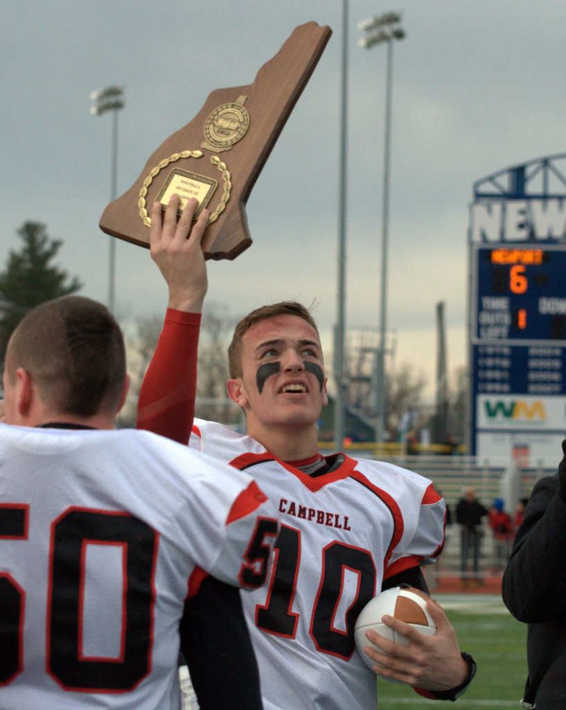 Campbell's Kyle Manning holds up the Division III championship plaque after the Cougars defeated Newport on Saturday.