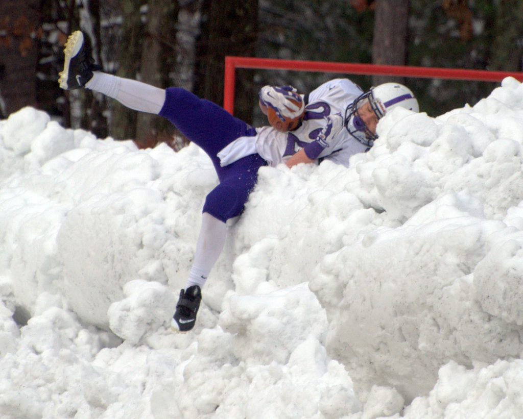 Nashua South's Josh Perry dives into a snowbank after scoring a touchdown during Thursday's game against Nashua North.