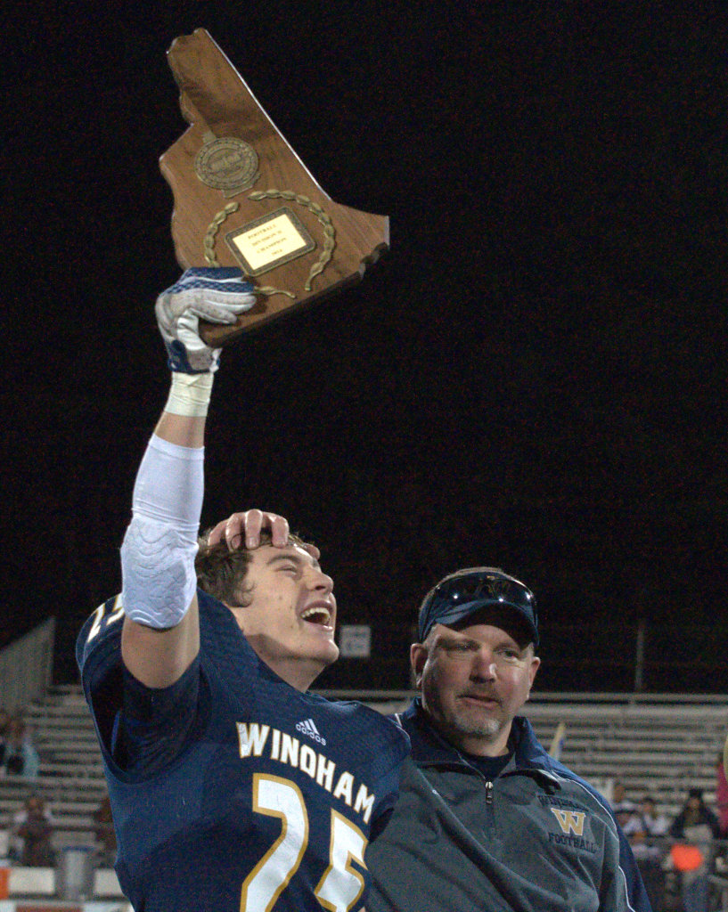 Windham's Kellin Bail holds up the Division II championship plaque as he celebrates with coach Bill Raycraft after Saturday's win.