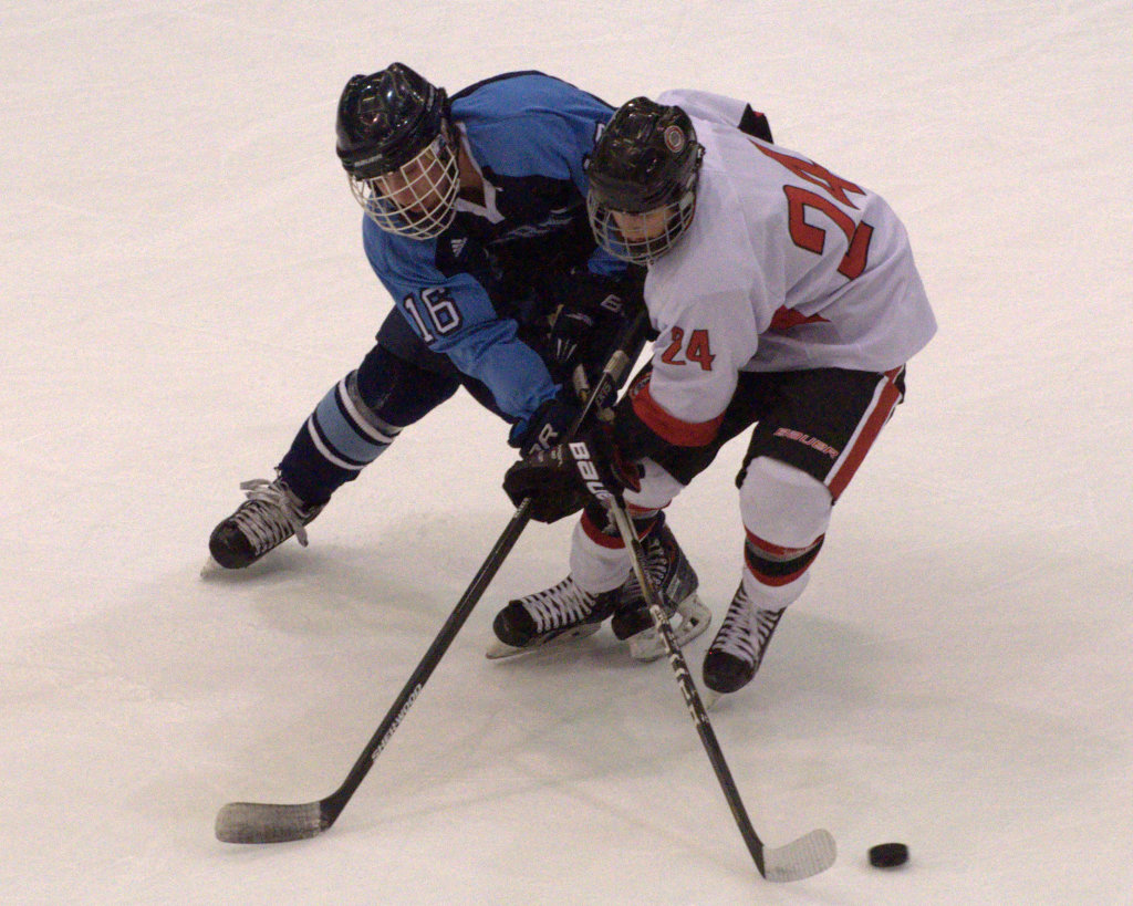 Nashua North's Robert LaVine knocks the puck away from Bedford's Jacob Rioux during Wednesday's game.