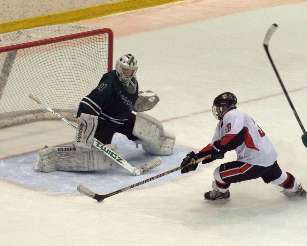 Bedford's Brett Veilleux moves in on Manchester Central goalie Mathieu Cislak during Saturday's game.