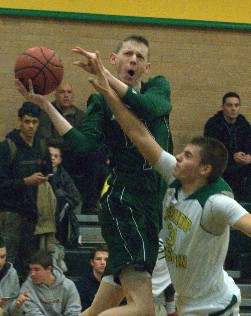 Bishop Guertin's Kyle Gavin fouls Pembroke's Max Curran during Monday's game.