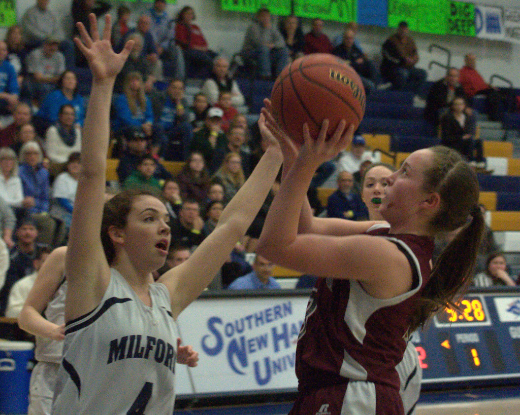 Goffstown's Sarah Doherty takes a shot as Milford's Adelle Pitsas defends during Thursday's semifinal. For more photos, go to the Photo Album.