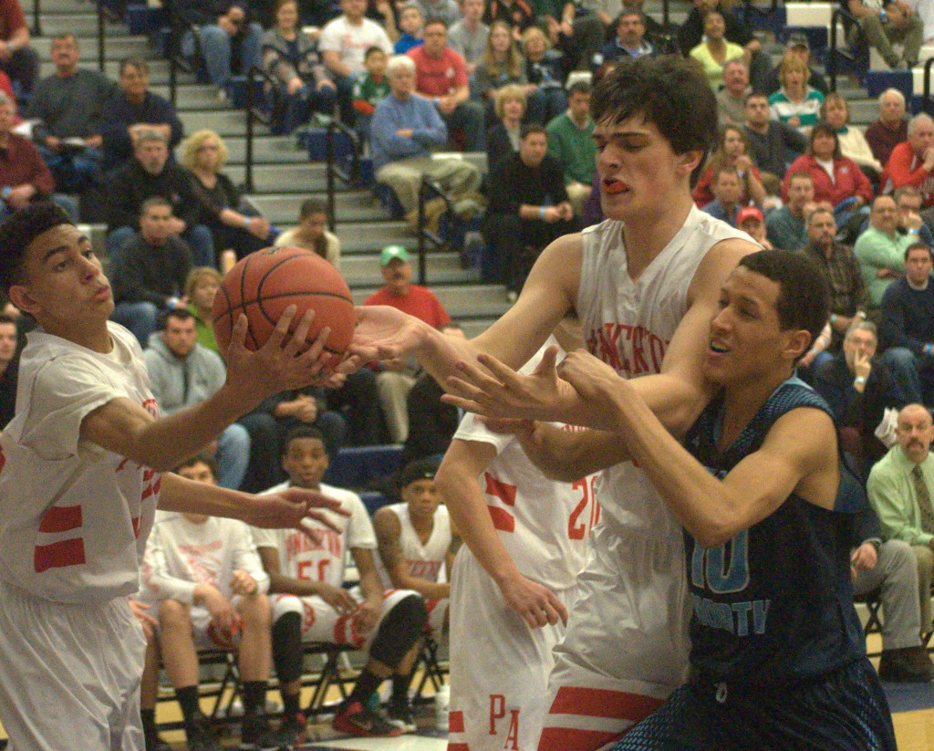 Pinkerton's Geo Baker, left, and Benjamin Olsen battle with Nashua North's Jefry Almonte for a rebound during Tuesday's game.