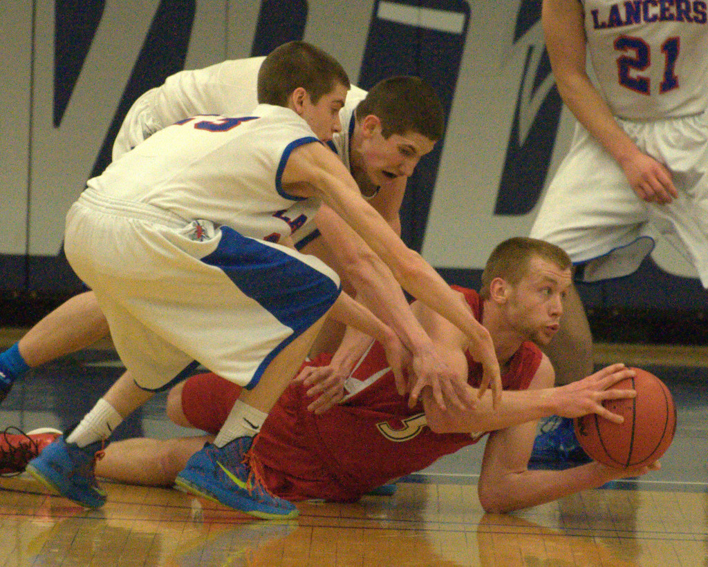 Spaulding's Darian Berry tries to get rid of the ball as Londonderry's Jacob Coleman, left, and Cody Ball reach for it during Tuesday's game.